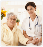 caregiver with stethoscope holding the hands of elderly patient