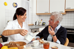 caregiver serving food to elderly patient