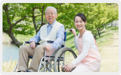 caregiver and patient on a wheelchair smiling