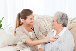 caregiver checking elderly patient's heartbeat