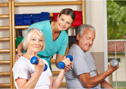 caregiver assisting elderly patients with their exercise